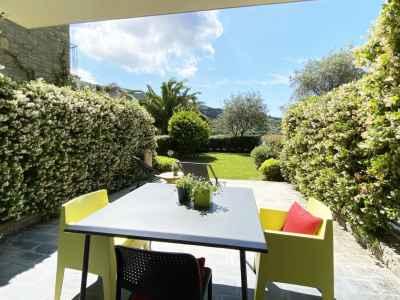 Terrasse couverte avec table et jardin fleuri