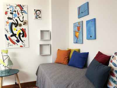 Holiday bed with pillows and colorful canvas